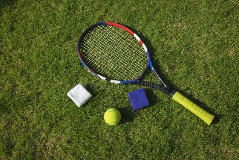 Tennisbollen, racket och armband på gräsfält grundar under solljus arkivfoto
