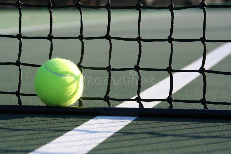 Tenniskugel gegen das Netz lizenzfreie stockbilder