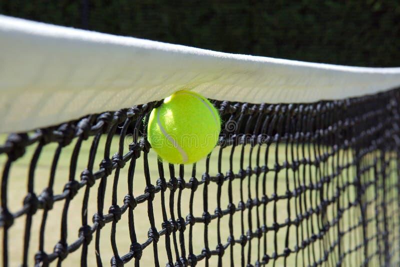 Tenniskugel im Netz. lizenzfreie stockbilder