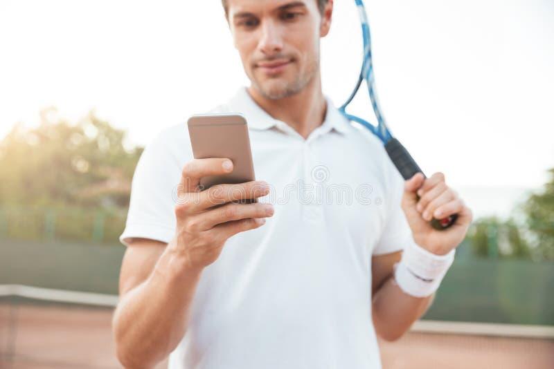 Tennisman med telefonen royaltyfri fotografi