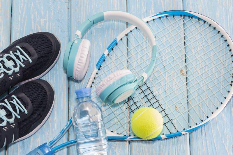 Tennisracket för fractalbild för bakgrund blå lampa gymnastikskor raket, boll, vattenflaska, musikhörlurar arkivfoton