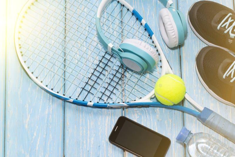 Tennisracket f?r fractalbild f?r bakgrund bl? lampa gymnastikskor raket, boll, vattenflaska, musikh?rlurar arkivfoton