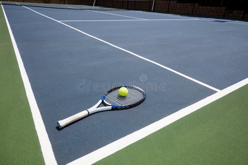 Tennisschläger und -ball vor Gericht lizenzfreie stockfotos