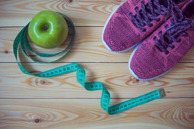 Tennisschoenen, centimeter en verse appel hoogste mening Gezond en activ royalty-vrije stock afbeeldingen