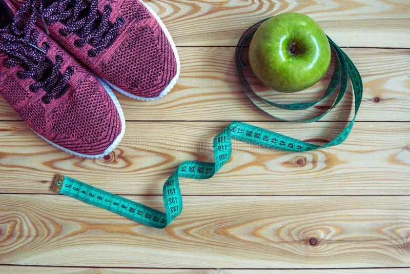 Tennisschoenen, centimeter en verse appel hoogste mening Gezond en activ stock afbeelding