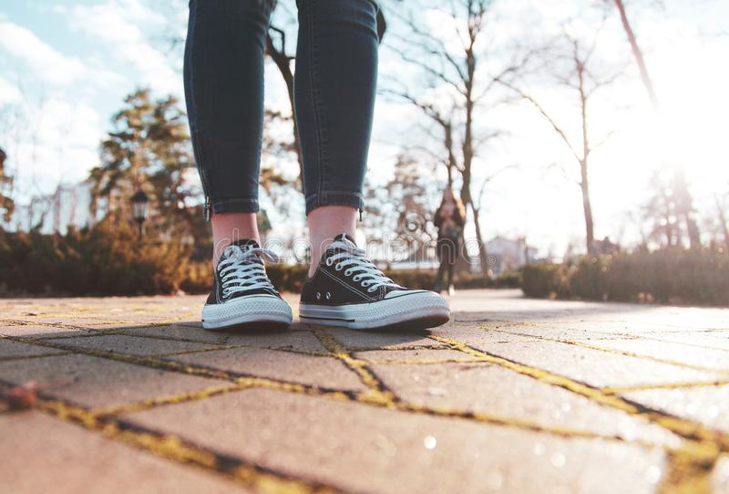 Tennisschoenen op de benen van een vrouw die in het park loopt royalty-vrije stock afbeeldingen