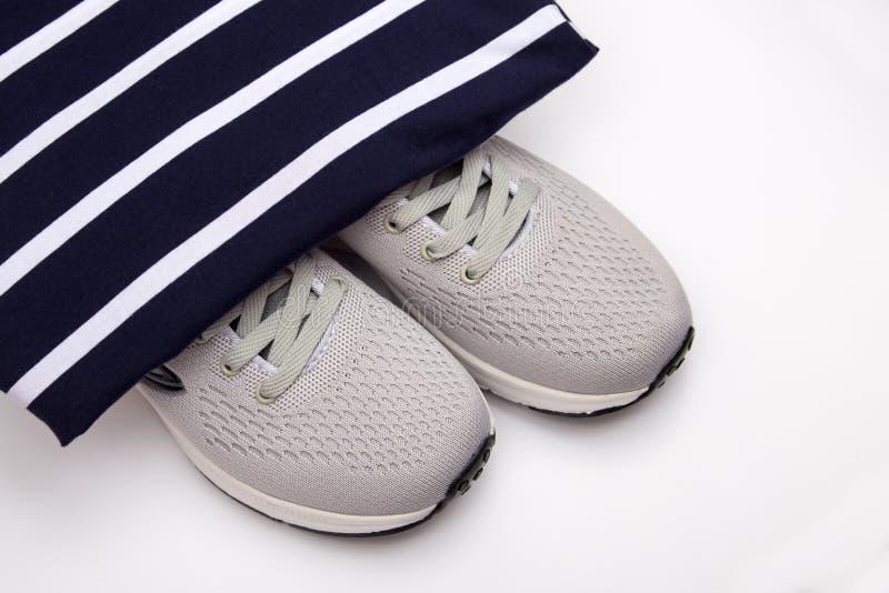 Tennisschoenen op een gestreepte achtergrond De manierschoenen van kinderen op een zwart-witte gestreepte achtergrond De schoenen stock afbeeldingen
