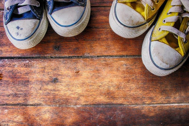 Tennisschoenen op houten vloer, vuile convasschoen op oud hout stock fotografie