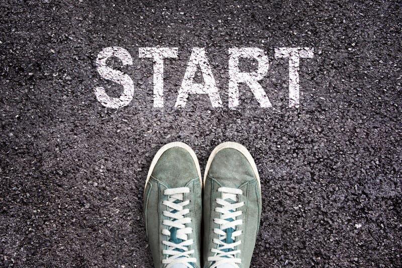 Tennisschoenschoenen en het woordbegin op asfaltgrond wordt geschreven, het nieuwe leven dat stock afbeeldingen