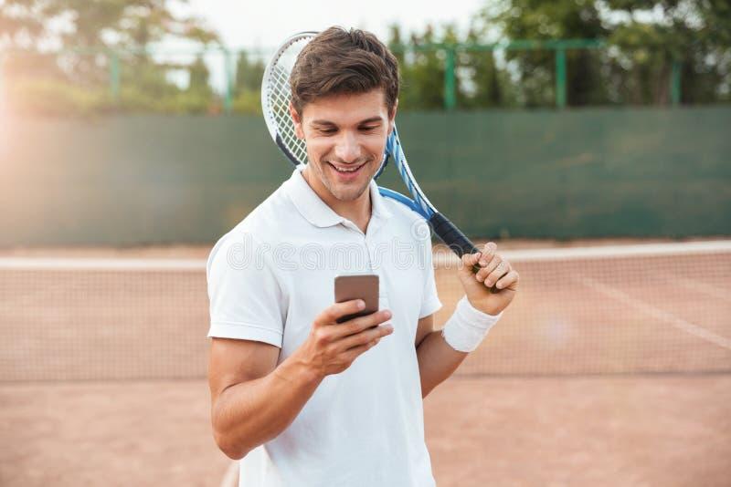 Tennisspelare med telefonen royaltyfria bilder
