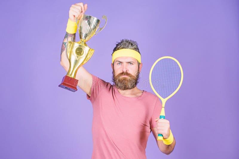 Tennisspieler-Gewinnmeisterschaft Athletengriff-Tennisschl?ger und goldener Becher Hippie-Abnutzungssportausstattung des Mannes b lizenzfreie stockfotografie