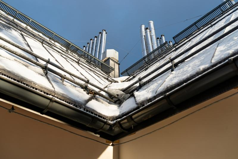 Tenntak på som ligger snön, den synliga fasaden av byggnaden, avloppsrännan, ventilationslampglasen och detsnö systemet arkivfoto