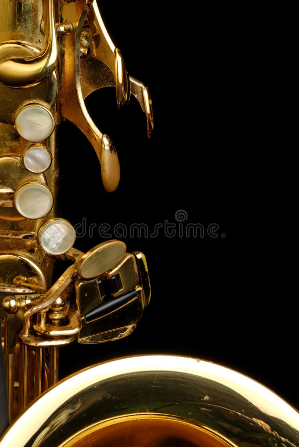 Tenor Saxophone. Close up of a well used tenor saxophone against a black background stock photo