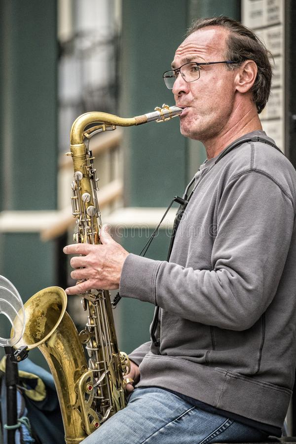 A tenor sax street performer in Quebec City. A tenor saxophonist street performer in Quebec City with very expressive face royalty free stock photography