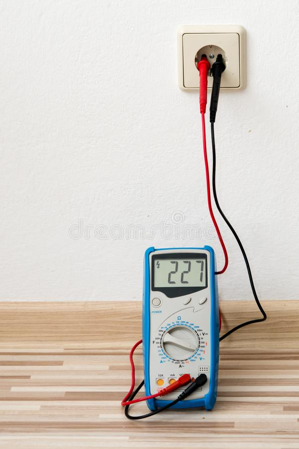 Tensão que mede com o instrumento do multímetro digital no soquete de parede fotografia de stock