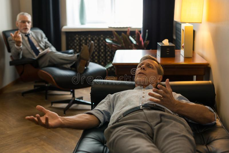 Tense Caucasian male patient complaining about his problems. Tense man. Tense Caucasian male patient lying on the couch in front of his psychotherapist while stock images
