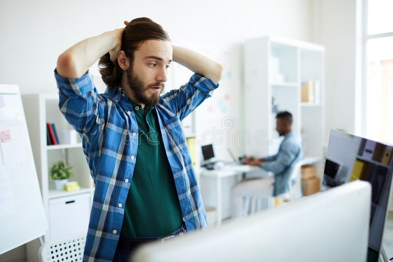Tense expression. Anxious young it-manager touching his head while looking at coded data on one of monitors royalty free stock image
