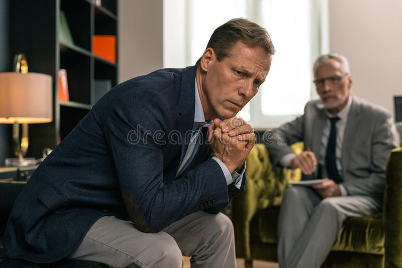 Tense sad brown-haired man sitting on the sofa. Sad man. Closeup portrait of a tense sad brown-haired men with a wedding ring sitting on the sofa royalty free stock photos