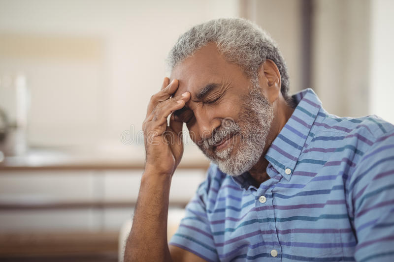 Tense senior man sitting in living room. At home stock image