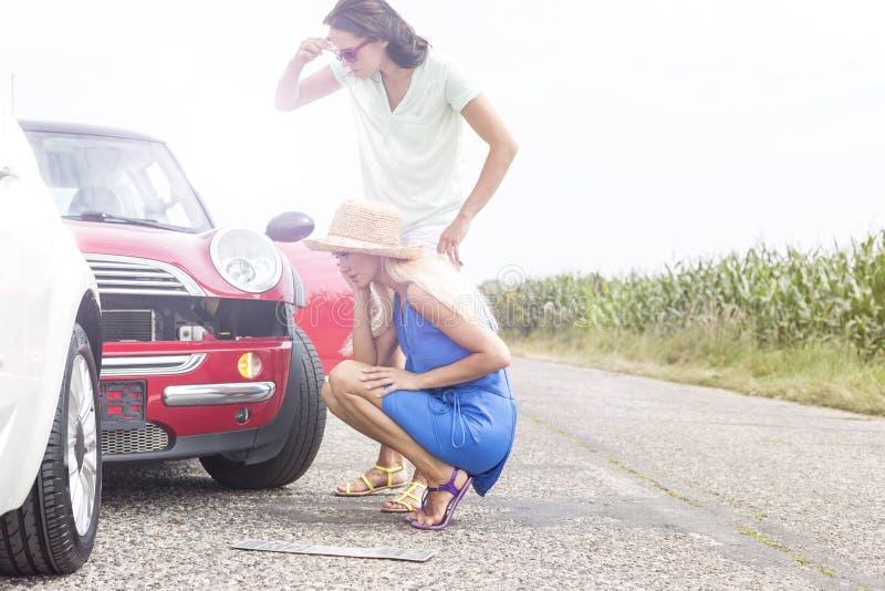 Tensed женщины смотря поврежденные автомобили на дороге против ясного неба стоковые изображения rf