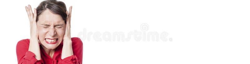 Tensed зубы молодой женщины меля, покрывая ее уши, длинная панорама стоковое фото