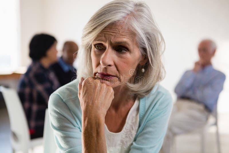 Tensed старшая женщина с друзьями в предпосылке стоковое изображение rf