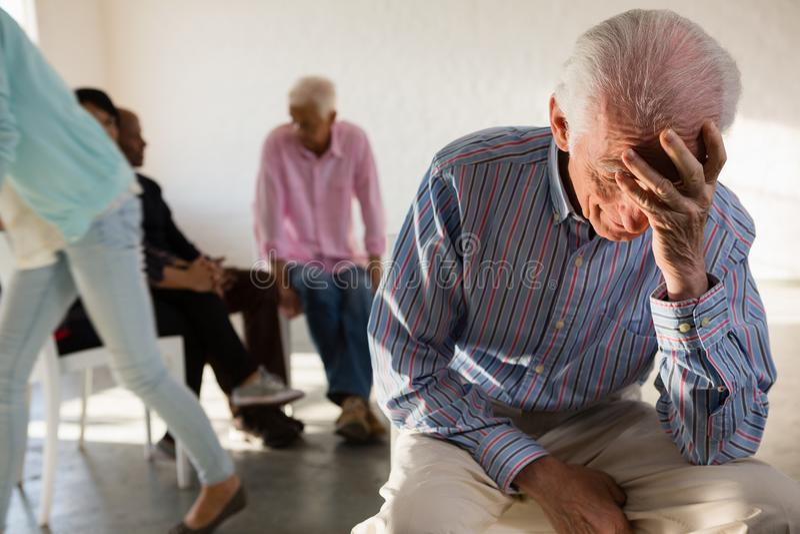 Tensed старший человек с друзьями в предпосылке стоковая фотография