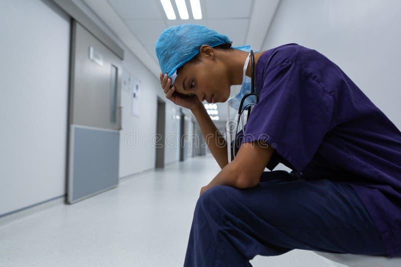 Tensed хирург с рукой на лбе сидя в коридоре больницы стоковые изображения