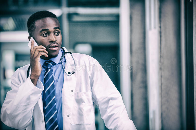 Tensed doctor talking on mobile phone. In hospital stock photos