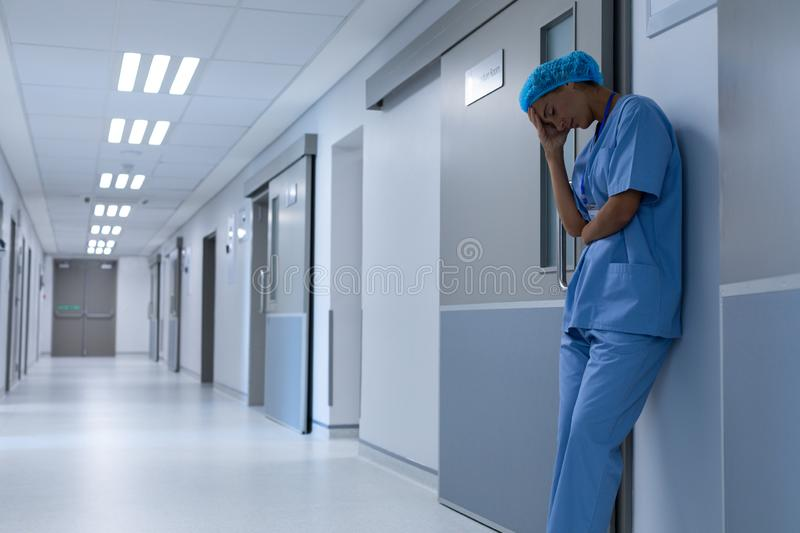 Tensed female surgeon with hand on head standing in the corridor at hospital royalty free stock photography