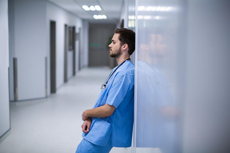 Tensed male nurse leaning on wall in corridor. Of hospital stock image