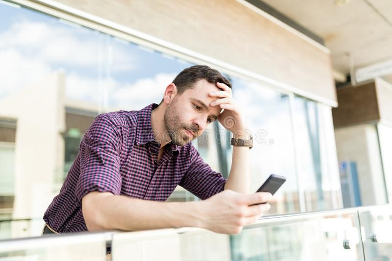 Tensed Man Reading Distressing News On Smartphone In Shopping Ma royalty free stock photos