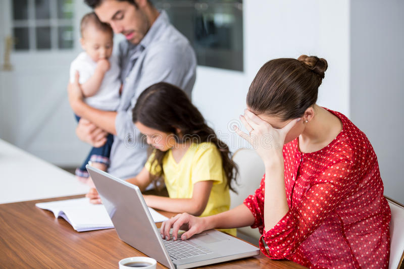 Tensed mother working on laptop with father helping daughter in homework. At home royalty free stock photography