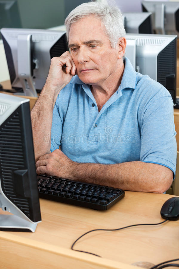 Tensed Senior Man Looking At Computer In Class stock photos