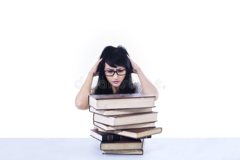 Tensión atractiva del estudiante que mira los libros - aislados imagen de archivo