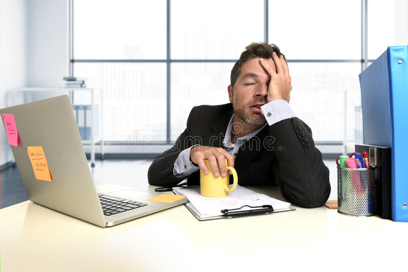 Tensión desesperada frustrada del sufrimiento de la expresión de la cara del hombre de negocios en el escritorio del ordenador de fotos de archivo libres de regalías