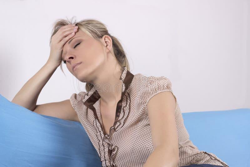 Tensión emocional, dolor de cabeza, mujer en casa en el sofá imagen de archivo