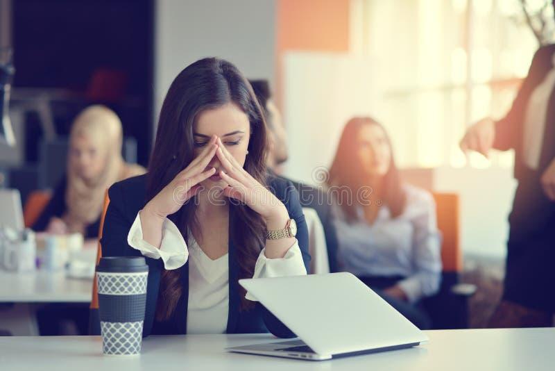 Tensión latina hermosa ocupada joven del sufrimiento de la mujer de negocios que trabaja en el ordenador de oficina imágenes de archivo libres de regalías