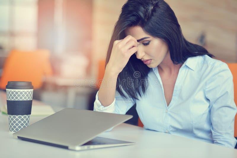 Tensión latina hermosa ocupada joven del sufrimiento de la mujer de negocios que trabaja en el ordenador de oficina foto de archivo libre de regalías