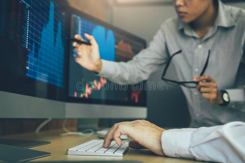 Tensi?n de dos agentes de bolsa del negocio y mirada de los monitores que exhiben la informaci?n financiera foto de archivo libre de regalías