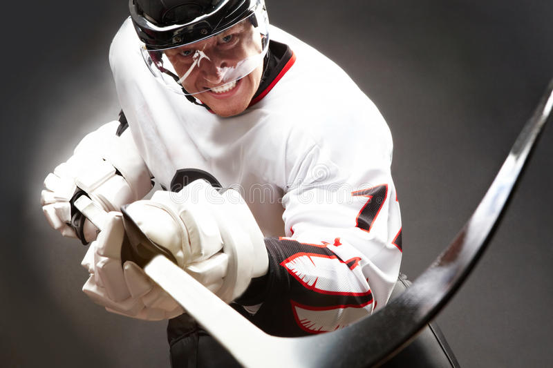 Tension. Hockey player with cruel facial expression pointing stick into camera royalty free stock photos