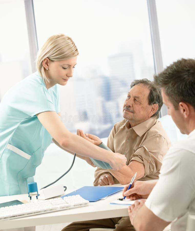 Tension artérielle de mesure d'infirmière de vieux patient images libres de droits