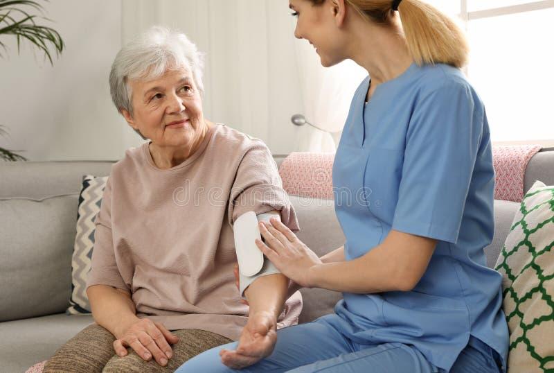 Tension artérielle de mesure d'infirmière de femme agée à l'intérieur photos stock