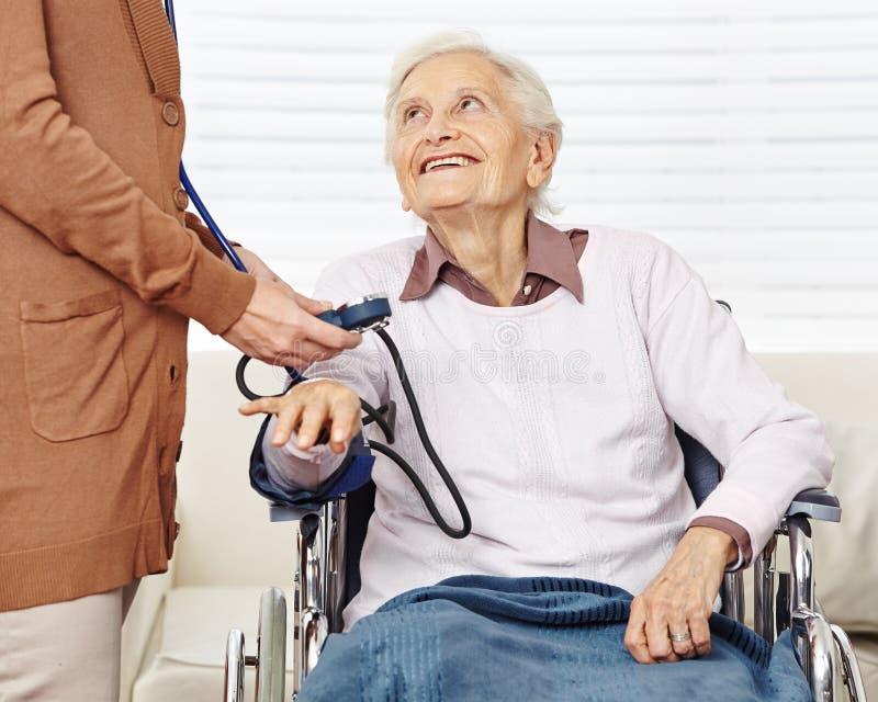 Tension artérielle de mesure d'infirmière pour photographie stock