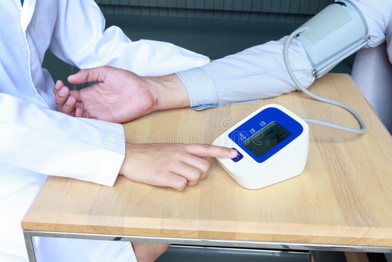 Tension artérielle de mesure de docteur de femme du patient images libres de droits