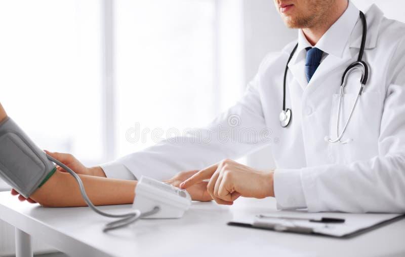 Tension artérielle de mesure de docteur et de patient photo libre de droits