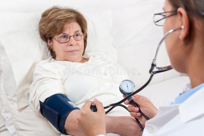 Tension artérielle de mesure de docteur sur le patient aîné image stock