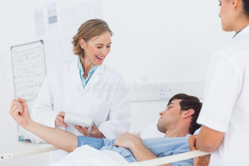 Tension artérielle de mesure de sourire de docteur d'un patient image libre de droits