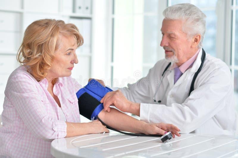 Tension artérielle de mesure de docteur de femme photos libres de droits