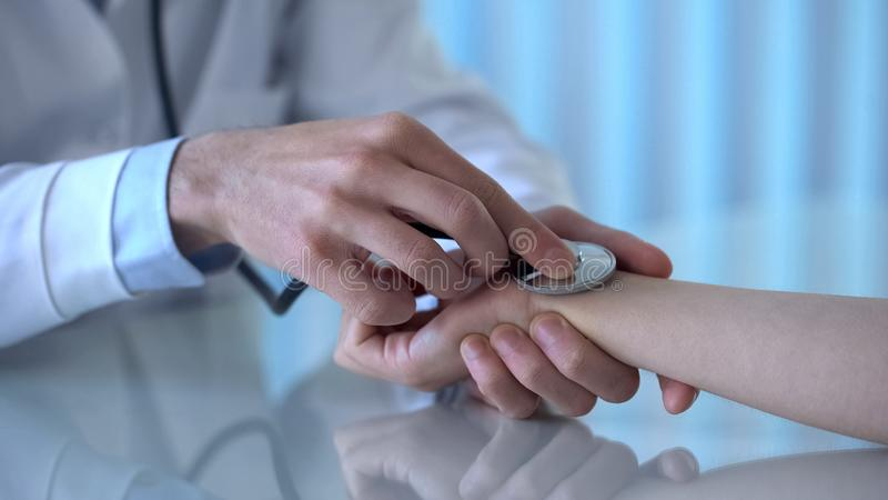 Tension artérielle de mesure de docteur masculin professionnel de patient féminin dans la clinique photographie stock